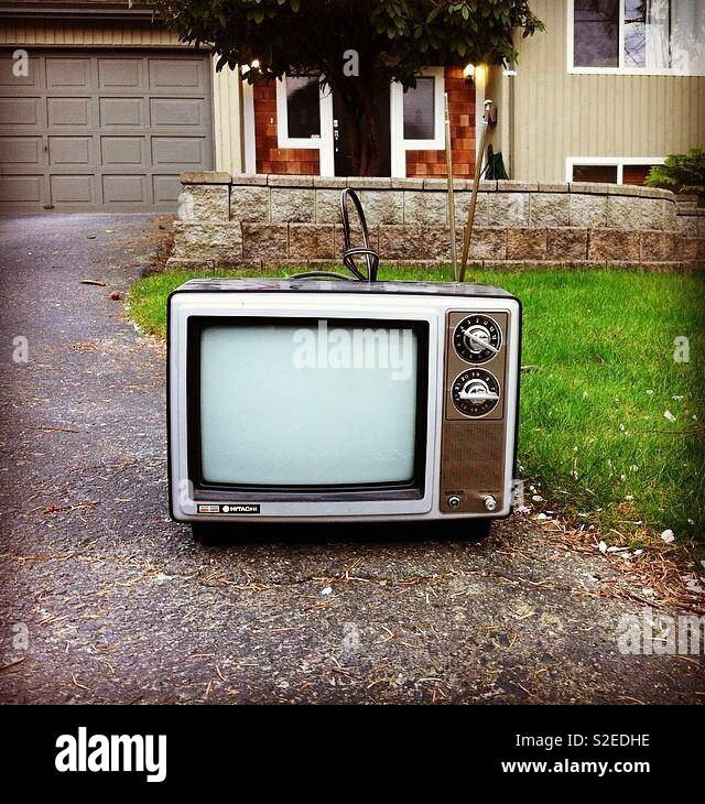 Old vintage TV with dials and antenna. On a driveway for junk pickup. - Stock Image