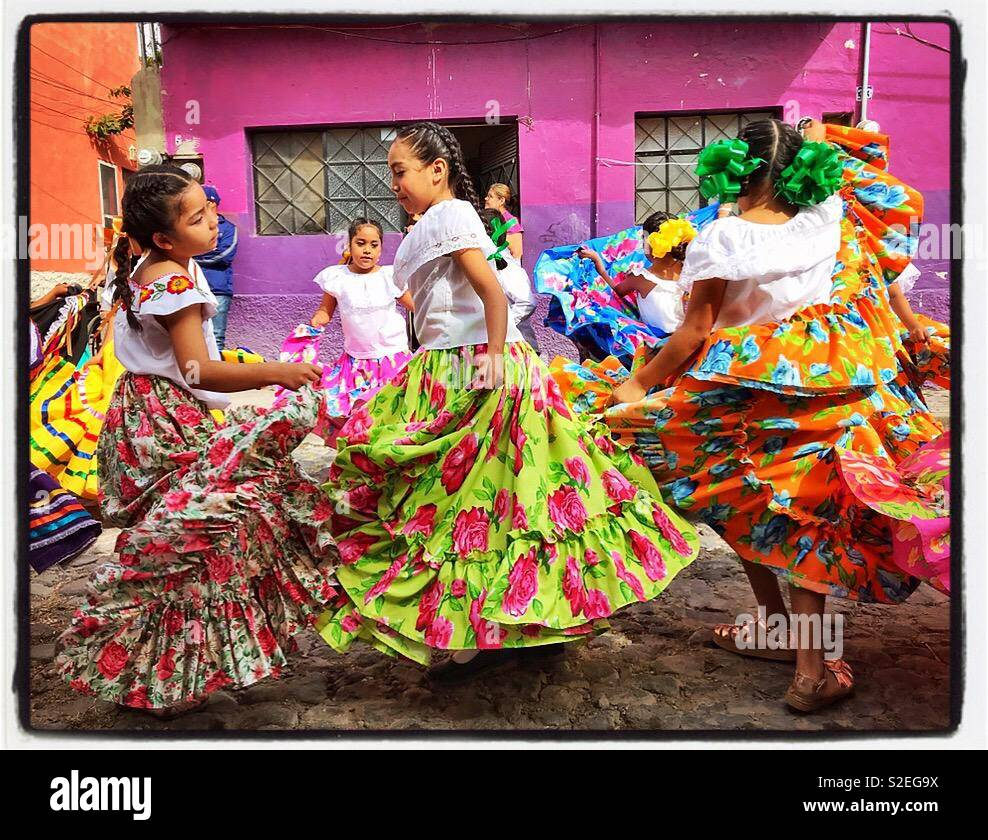 Girls in colorful swirling skirts dance on the cobblestone streets during a Revolution Day parade in Mexico. - Stock Image