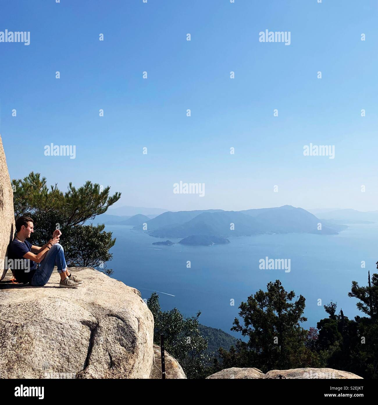 Traveller resting on top of Mount Misen, Miyajima, Japan - Stock Image