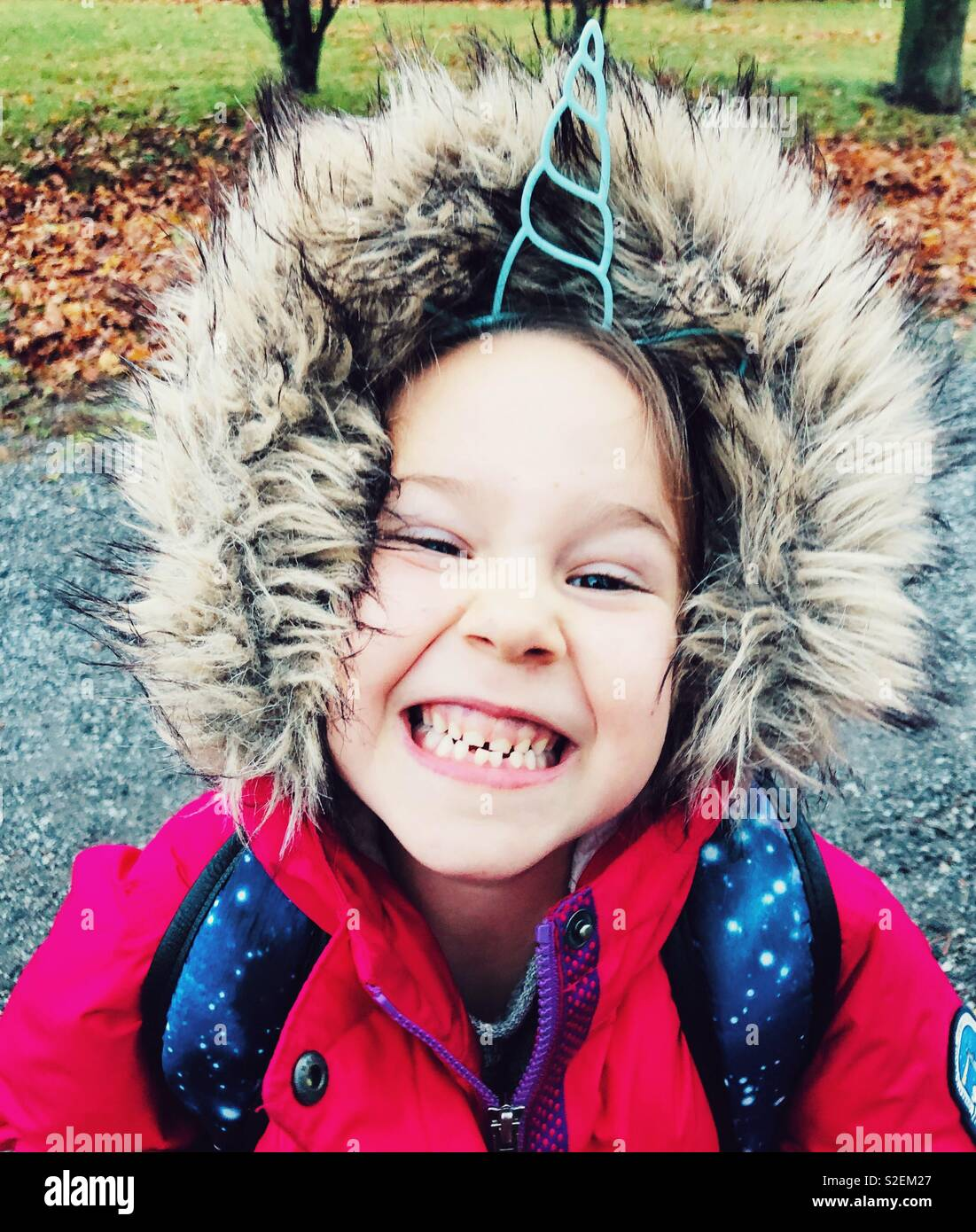 Portrait of a smiling 6 year old girl wearing unicorn horn headband and pink winter coat with furry hood - Stock Image