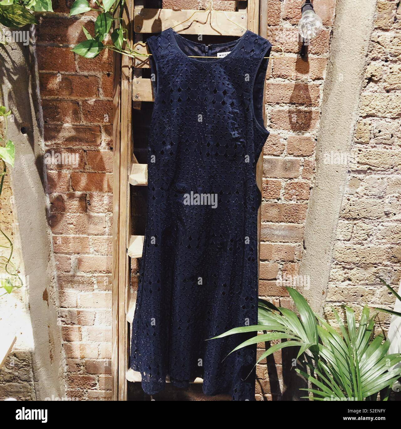 Navy blue occasion dress hanging on vintage ladder against stone colored brick wall - Stock Image