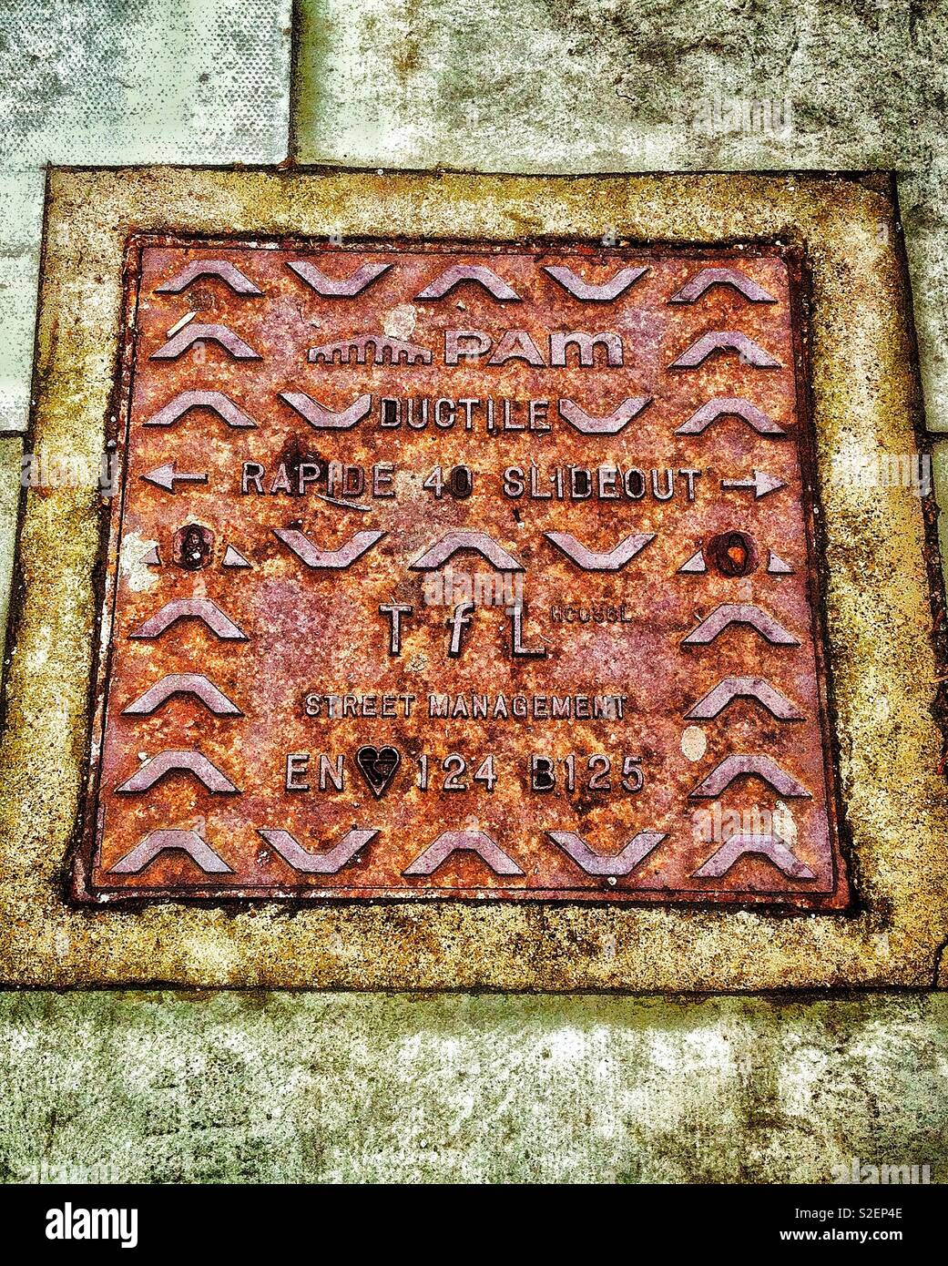 Cast iron utilities access cover set in a London pavement - Stock Image
