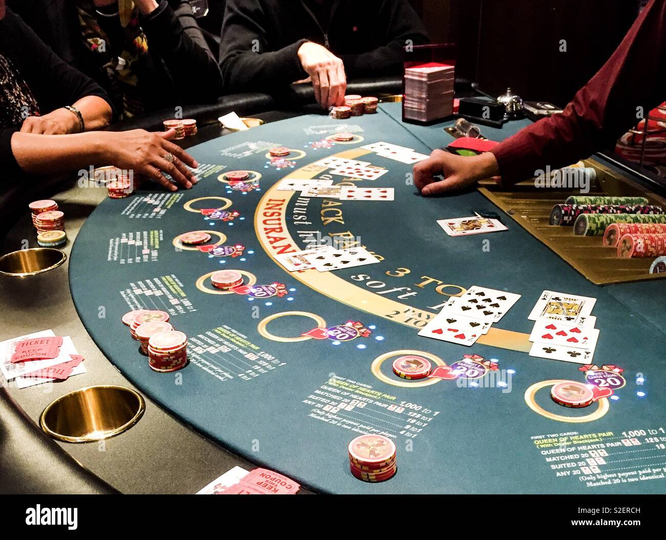 Life's a gamble as the players place their bets at the blackjack table. - Stock Image