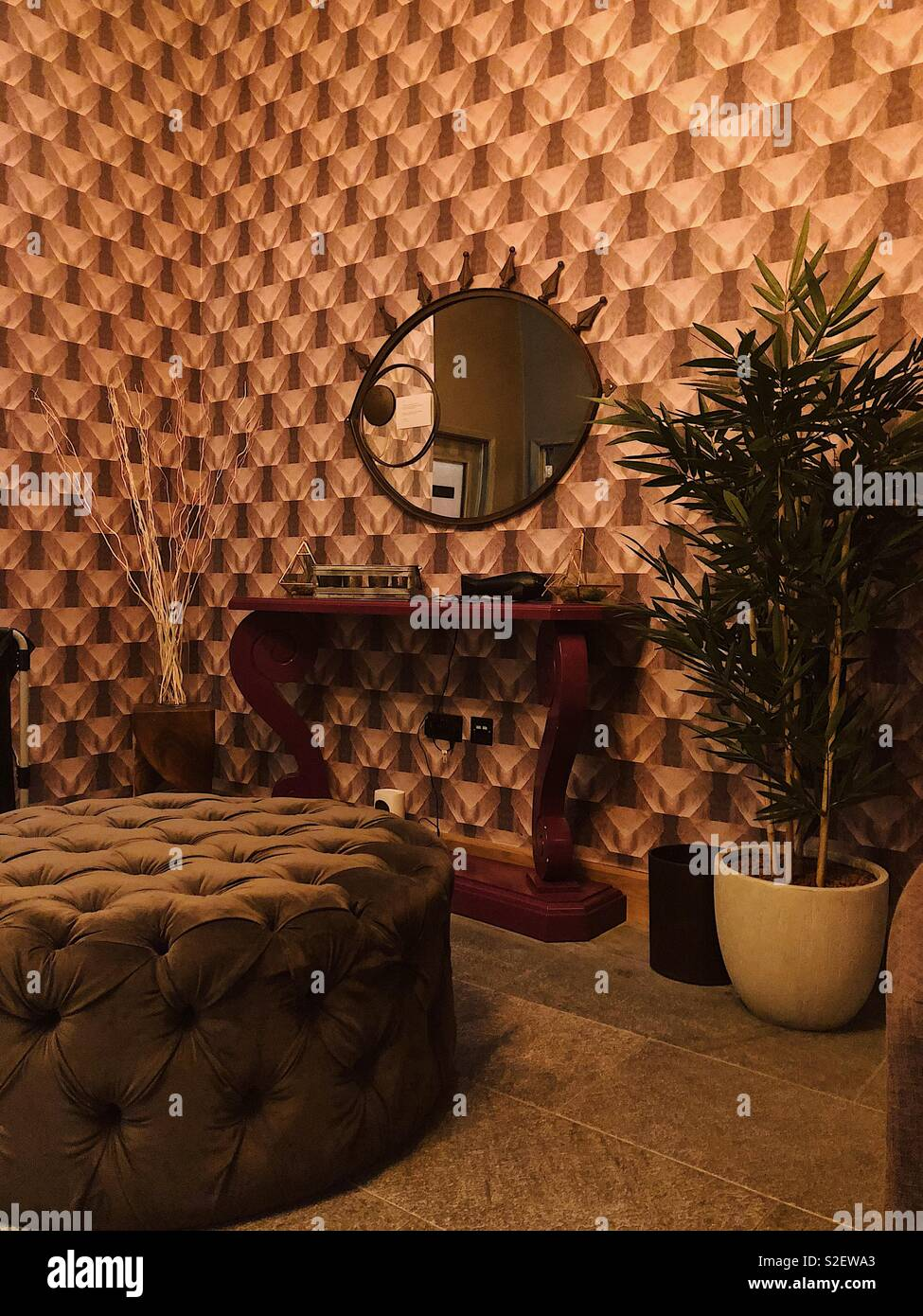 Relaxation area at the spa in seventies style with maroon toned geometric print wallpaper, palm plant and velvet poof - Stock Image