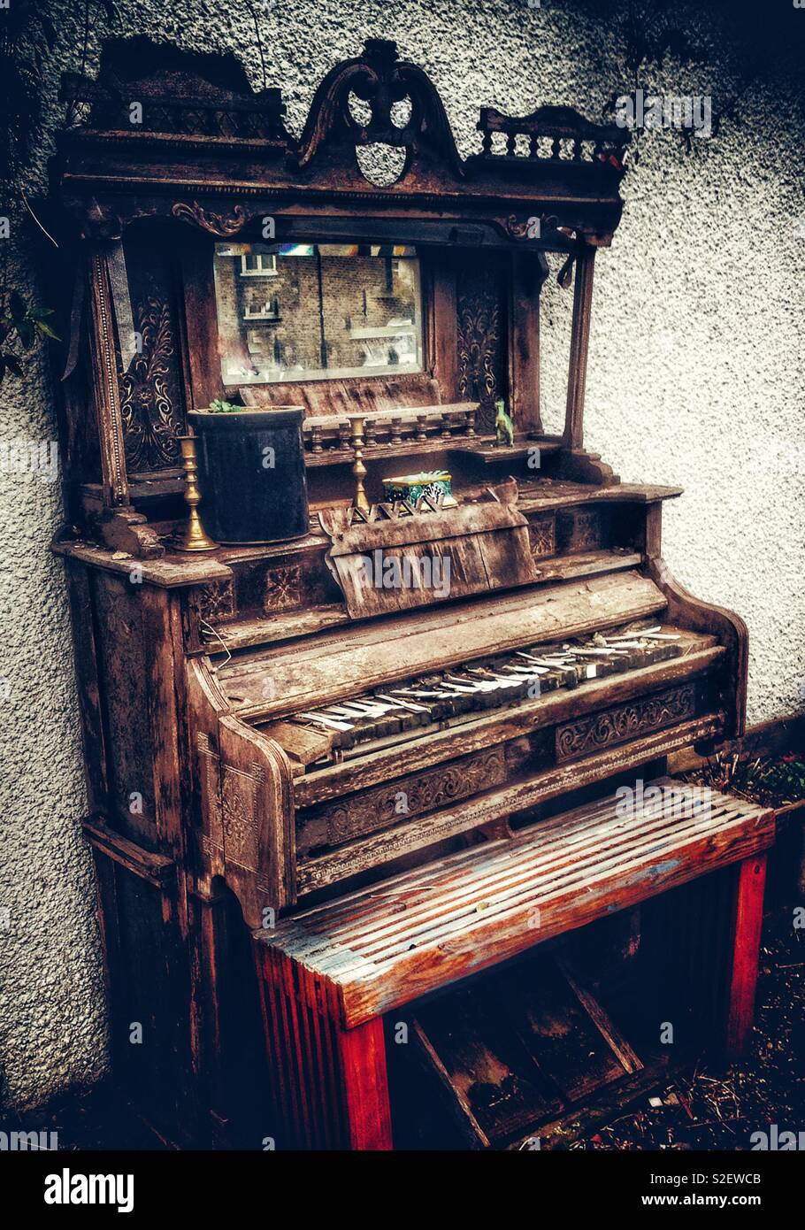 Dilapidated old pump organ being used as an unusual garden curiosity - Stock Image
