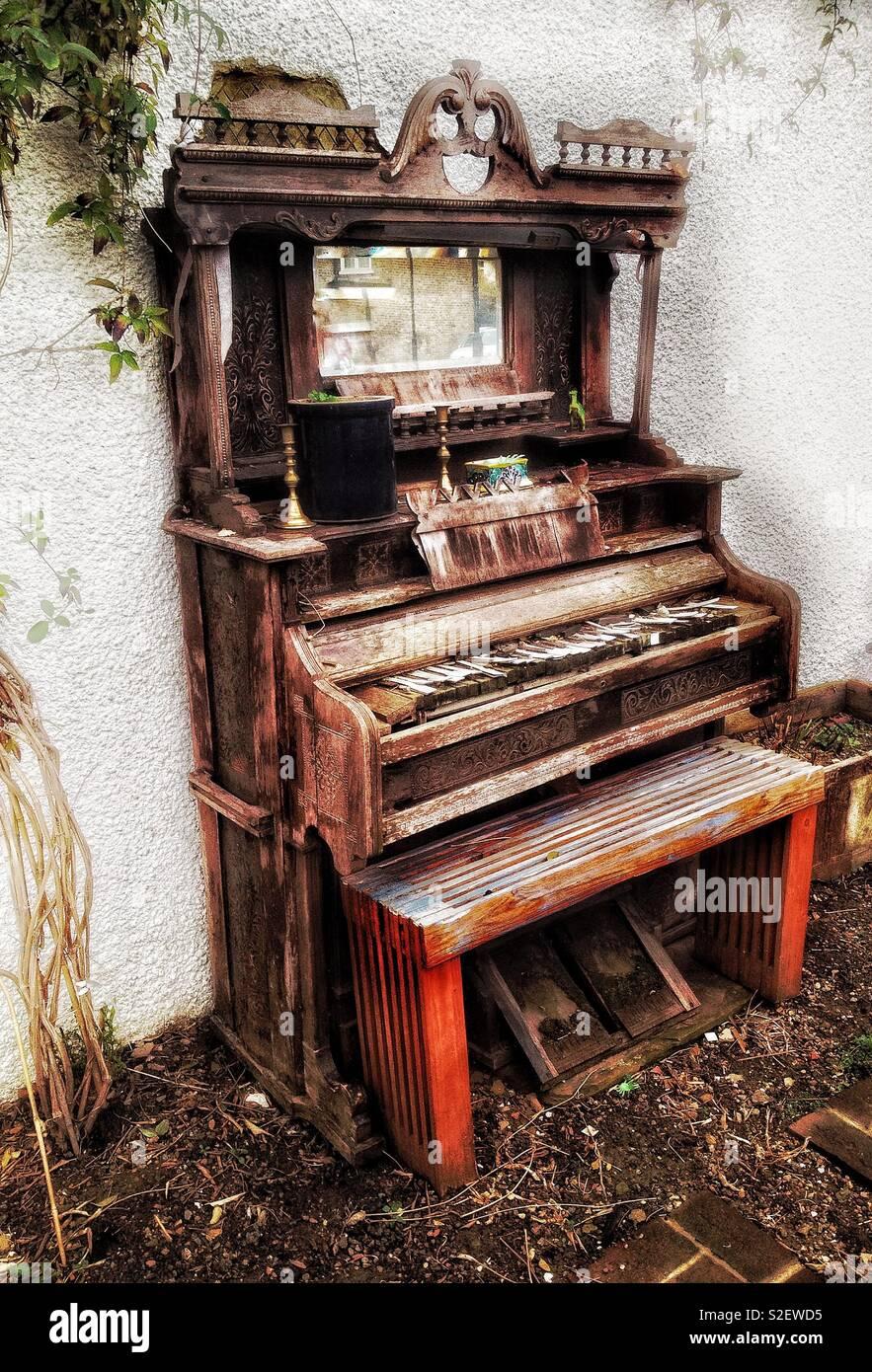 Sad old dilapidated pump organ being used as unusual garden furniture - Stock Image