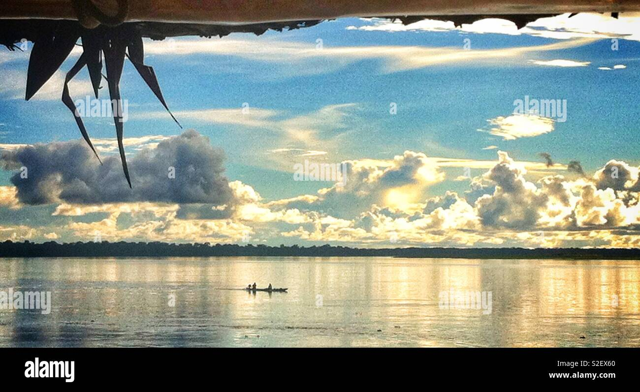 Small boat on the mighty Amazon river in Peru with a beautiful sky - Stock Image