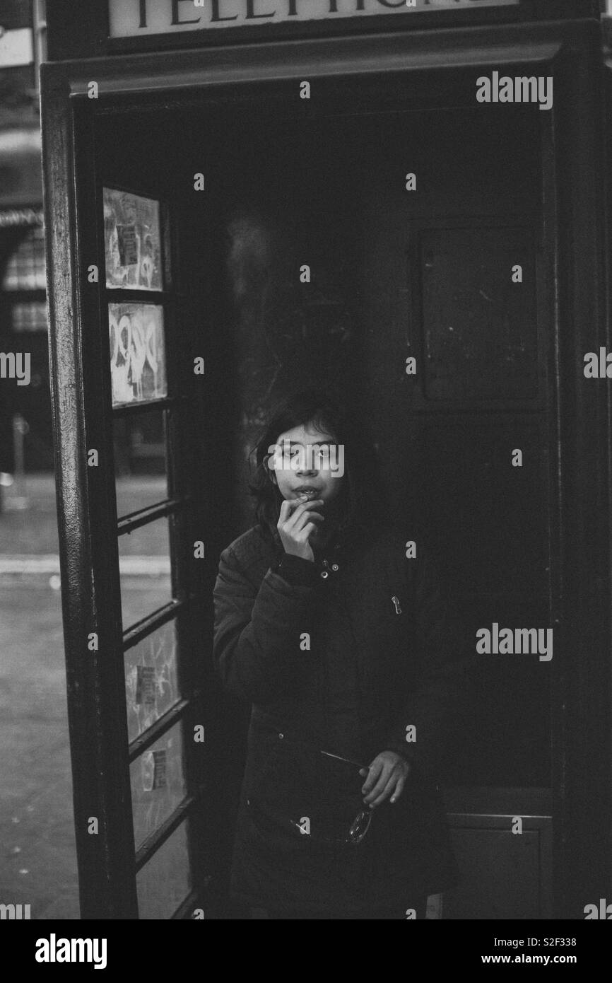 Little girl in a black London Telephone booth - Stock Image