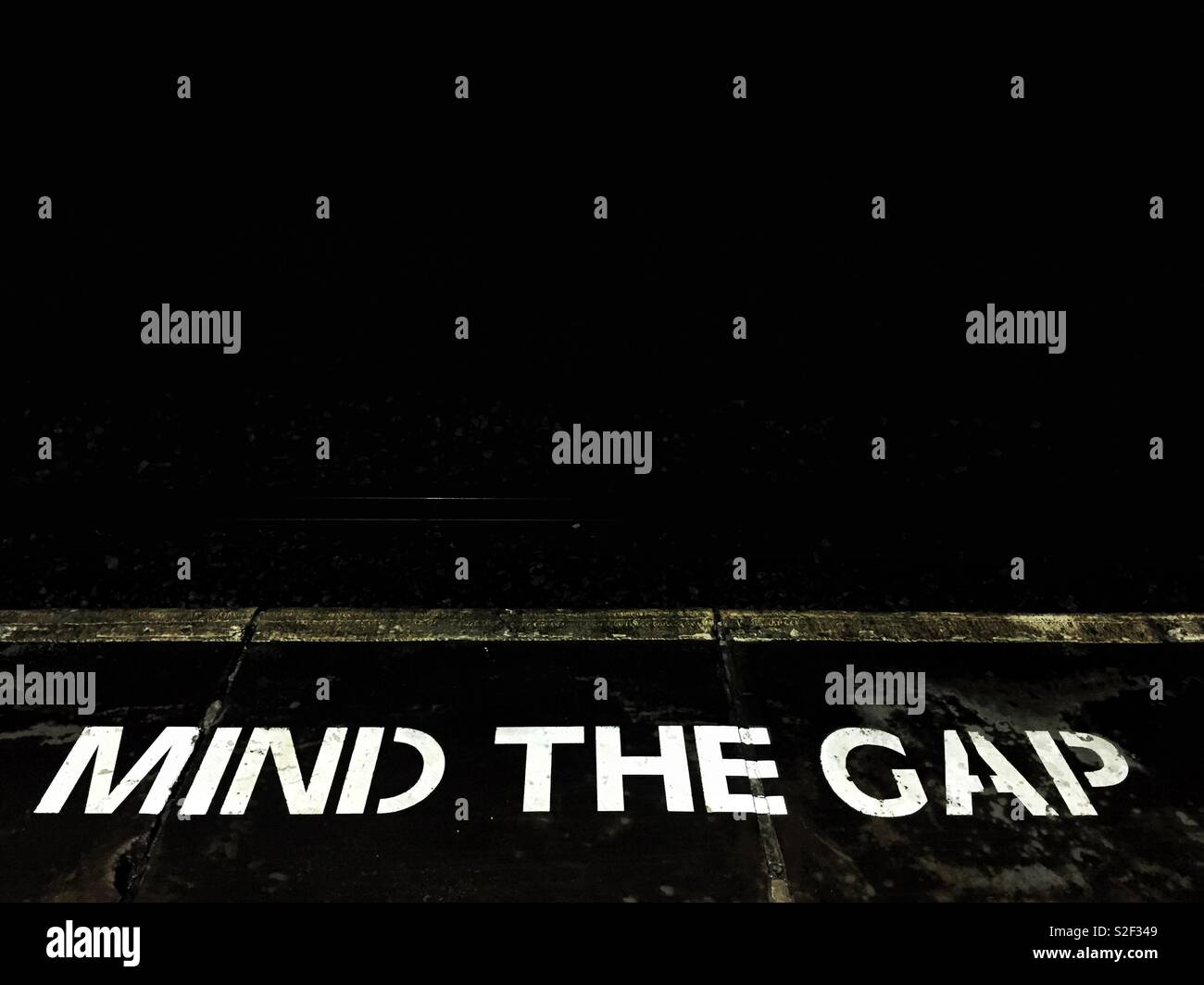 A sign on the floor of a railway station platform warning passengers to mind the gap - Stock Image