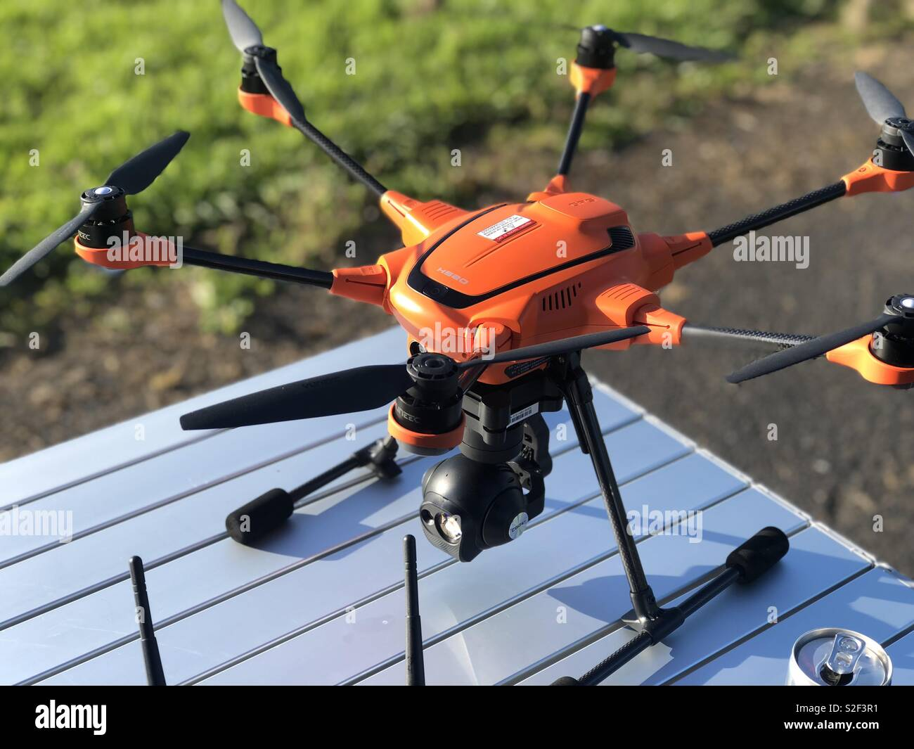 Orange hexacopter with gimbal controlled camera - Stock Image