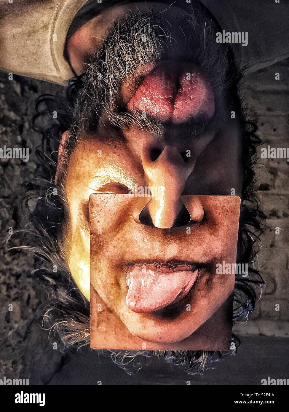 Surreal upside down man's face with two mouths pulling tongues - Stock Image