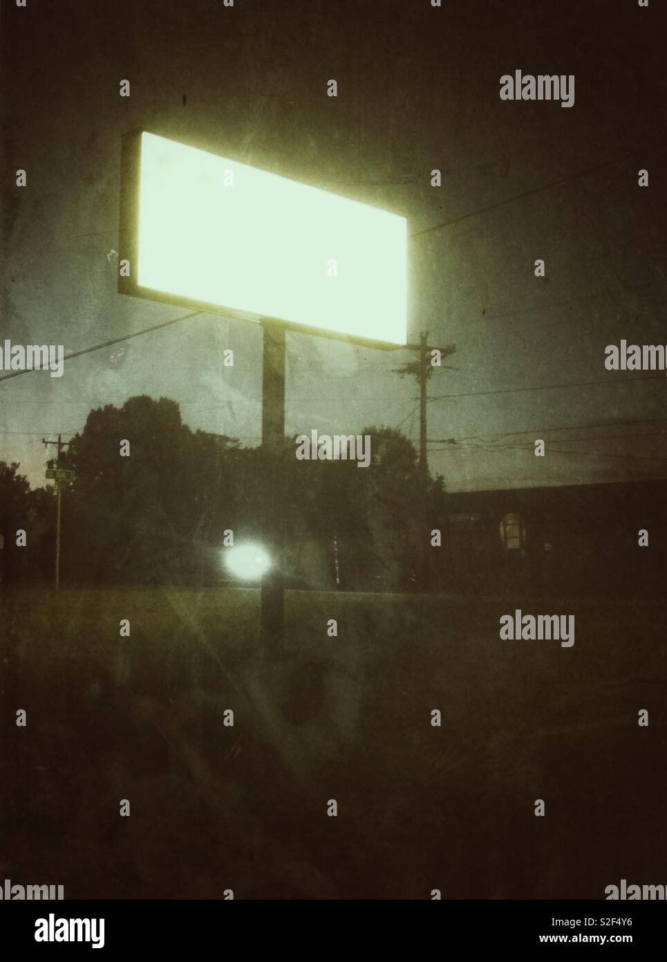 Monochromatic grunge photo of blank, eerie lighted store sign at twilight - Stock Image