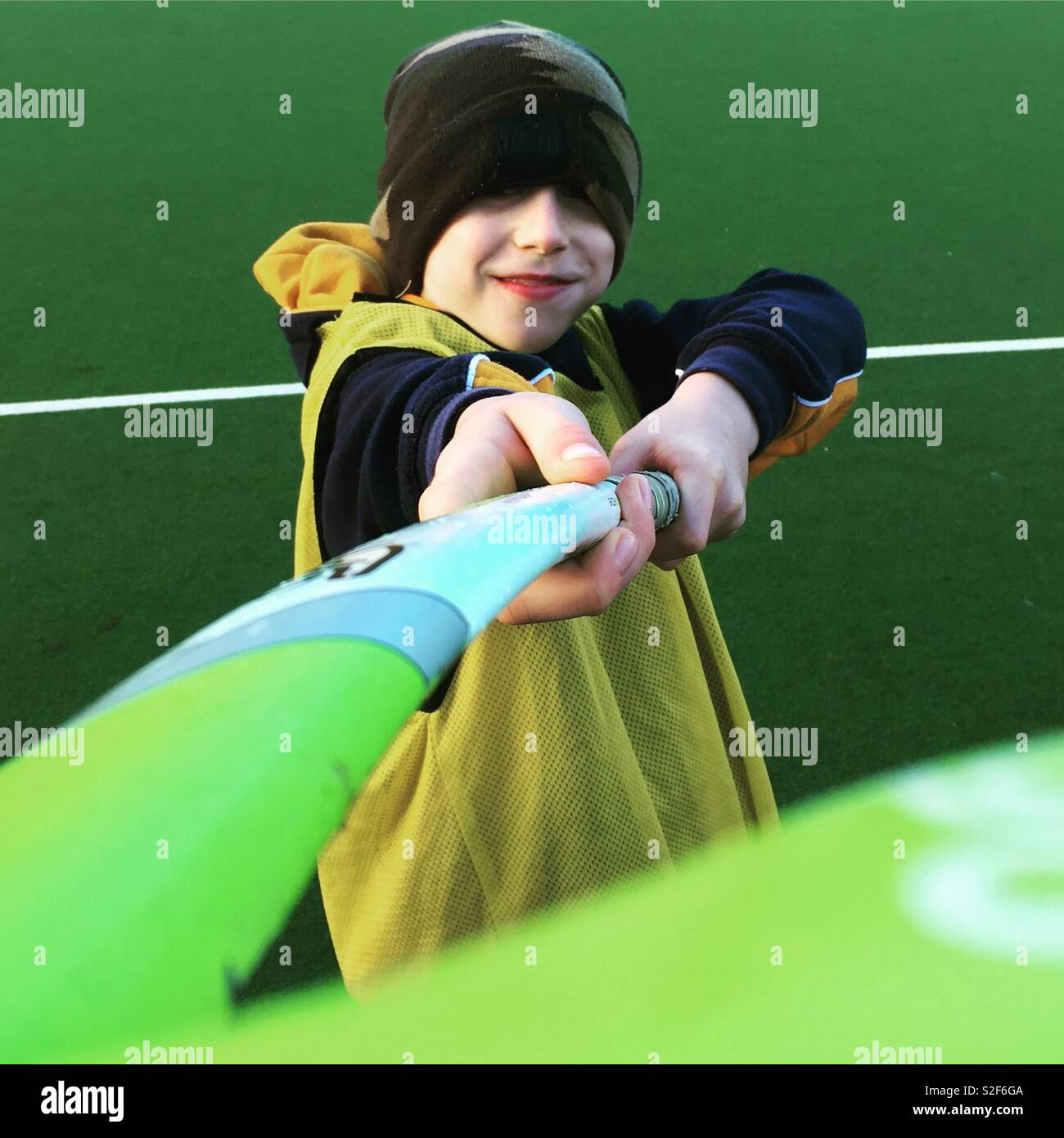Nine year old boy playing hockey on a AstroTurf pitch. Stock Photo