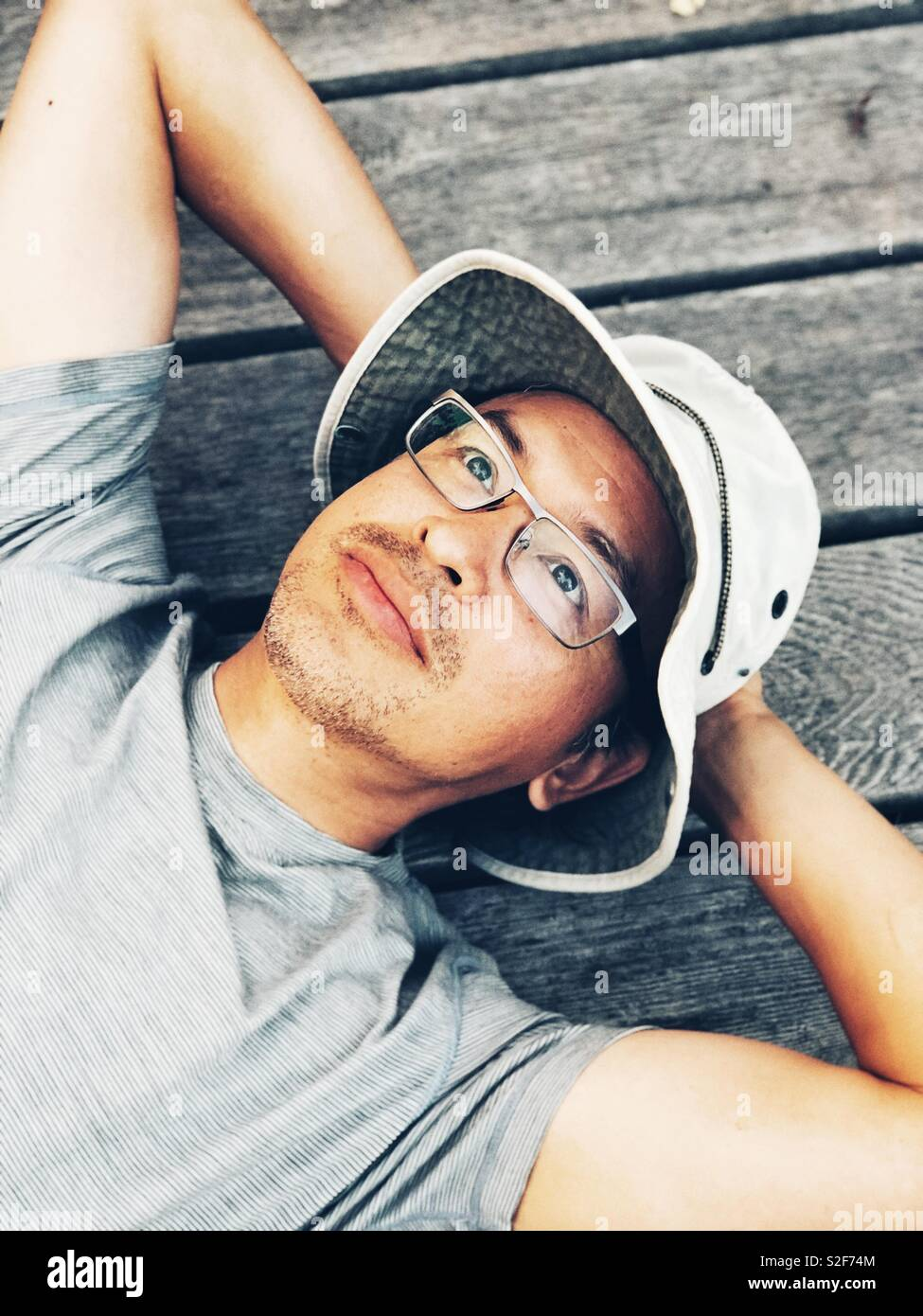 Middle aged Asian man wearing bucket hat and glasses looking up laying on camping platform in Canadian wilderness - Stock Image