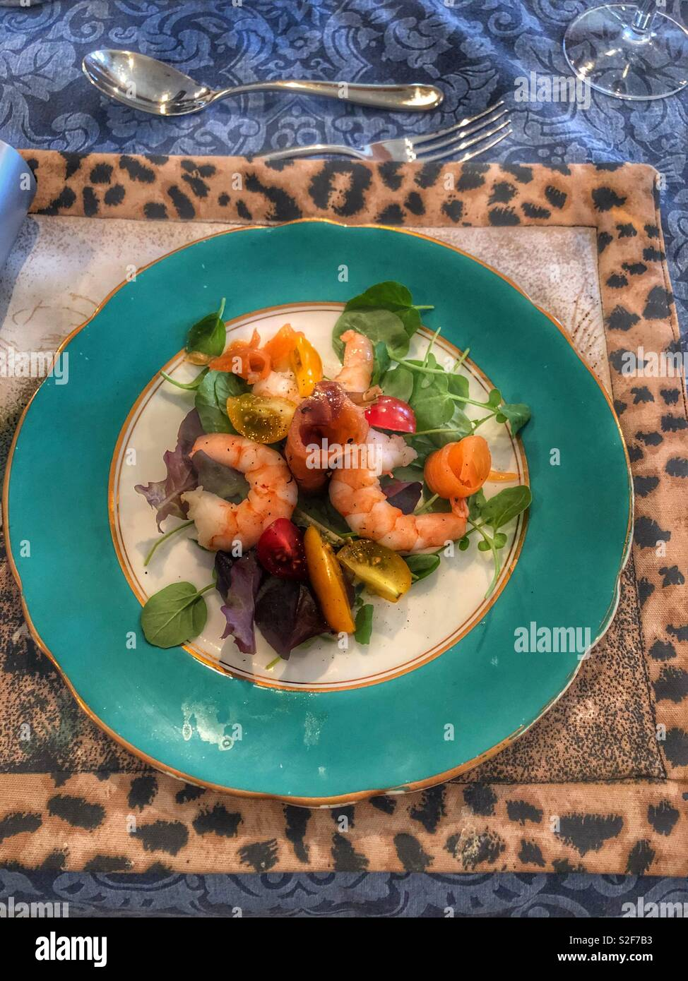 Prawn and smokes salmon salad appetiser on vintage jade plate with gold rim and leopard print place mat - Stock Image