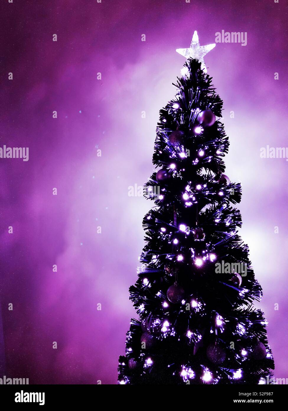Glowing Black Christmas Tree With Silver Decorations And Purple Glow Stock Photo Alamy