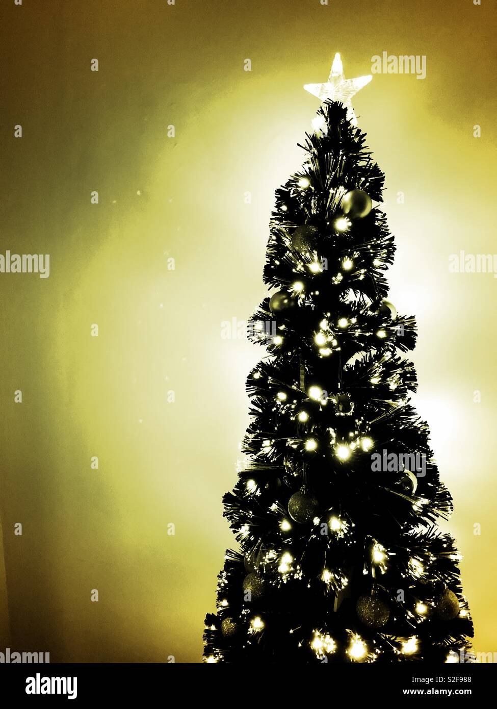 Glowing Black Christmas Tree With Silver Decorations And Golden Glow
