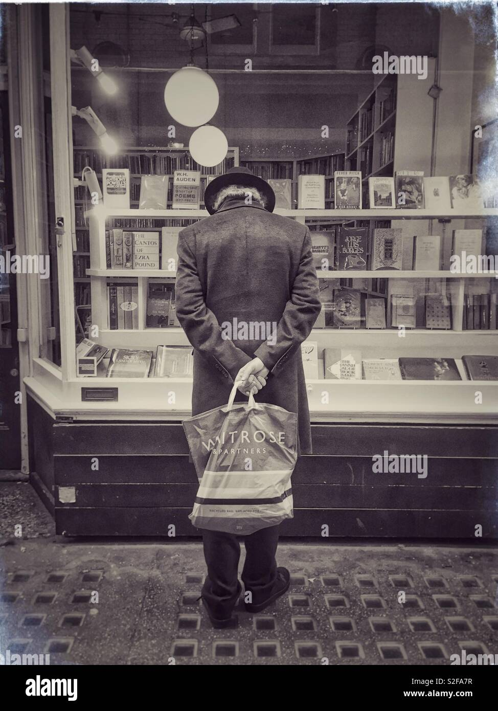 Old man window shopping outside a secondhand bookshop in Cecil Court, London. - Stock Image