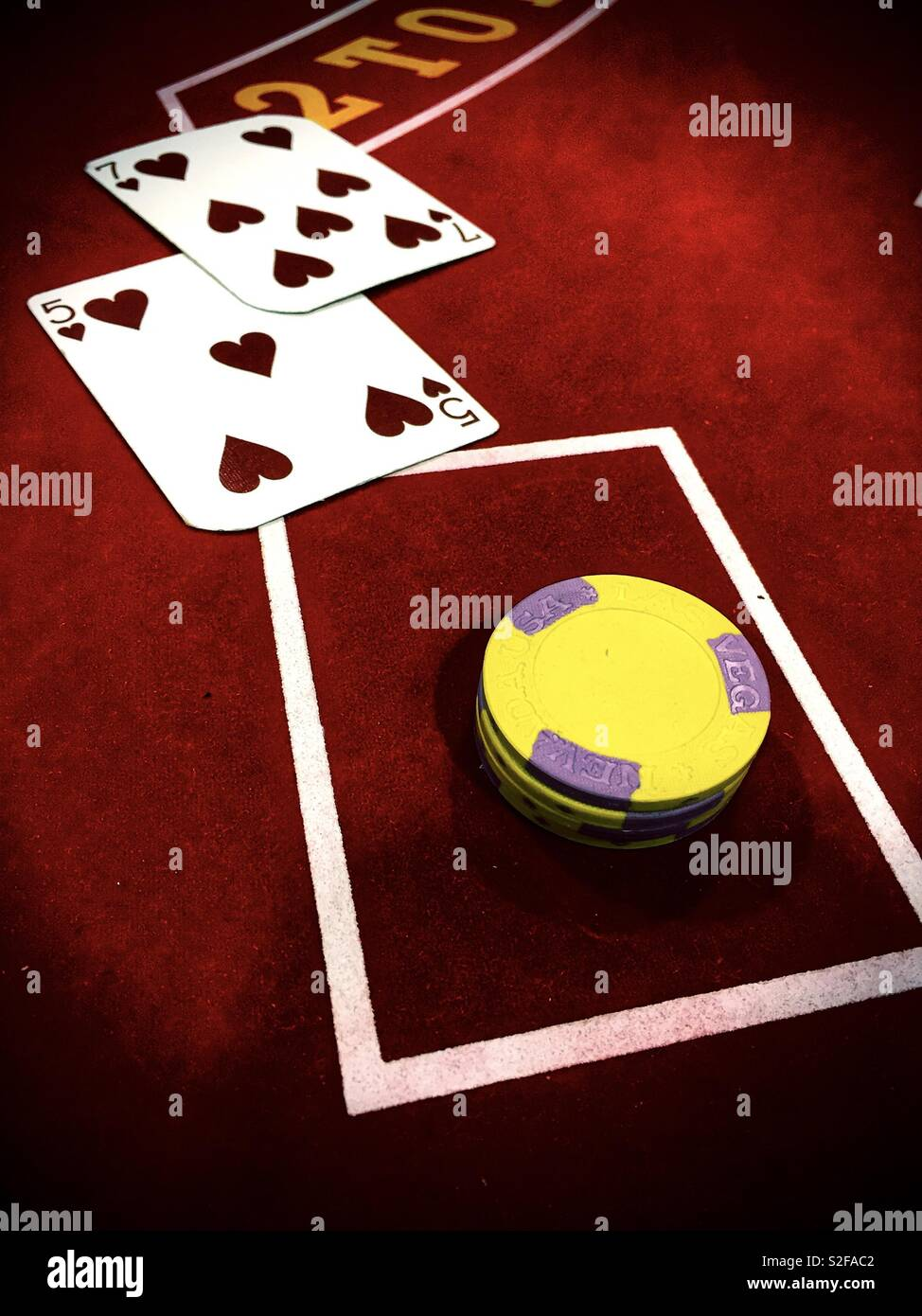 Betting chips and playground bag cards and a blackjack tables - Stock Image