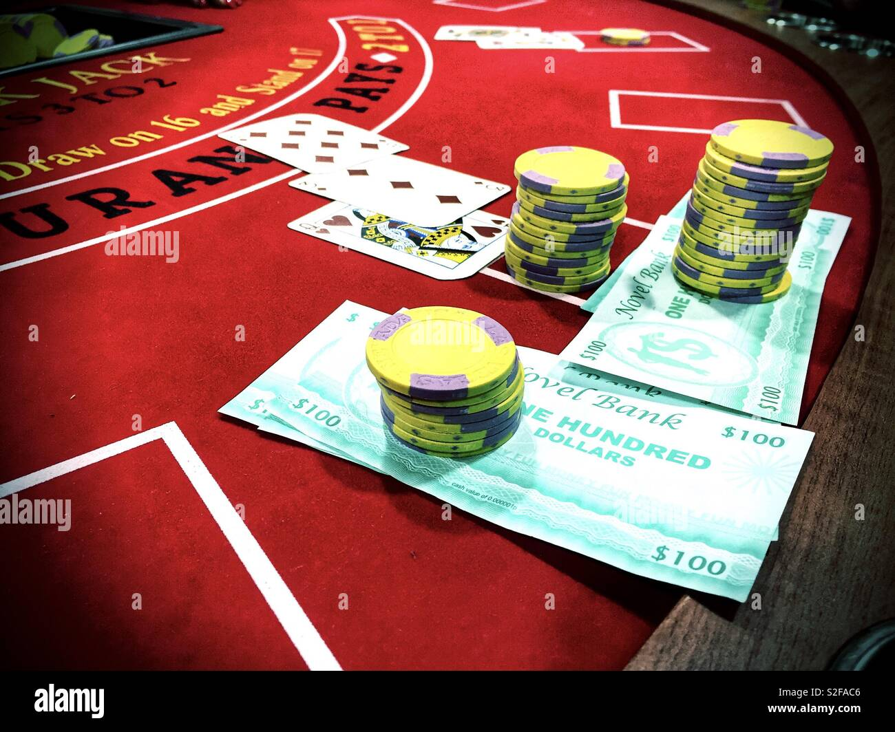 Chips. pretend money and playing cards on a blackjack table. - Stock Image