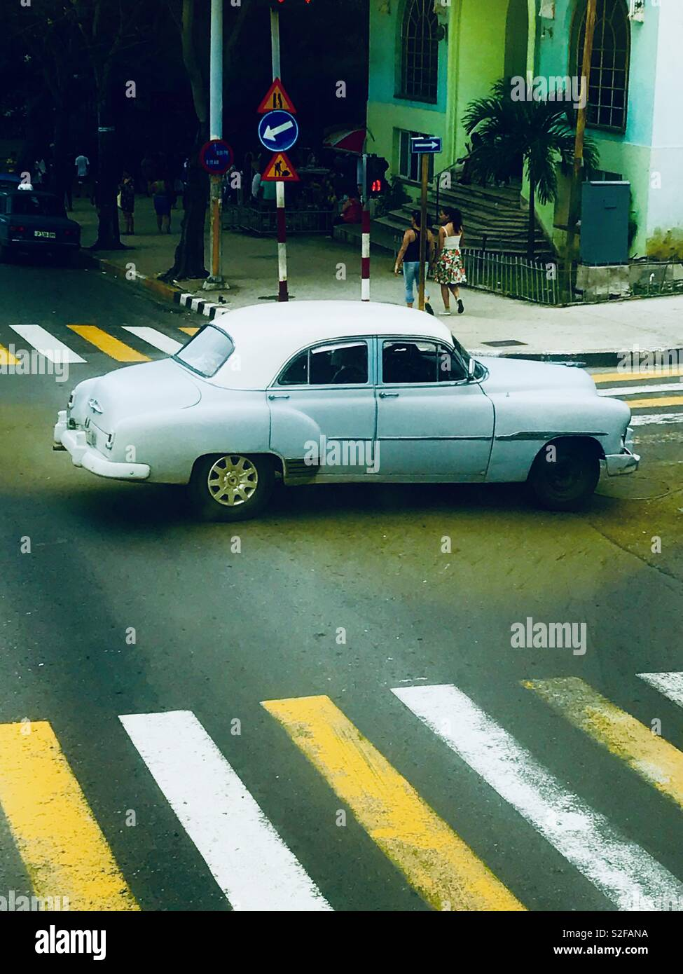 White classic car driving through the busy streets of Havana Cuba - Stock Image