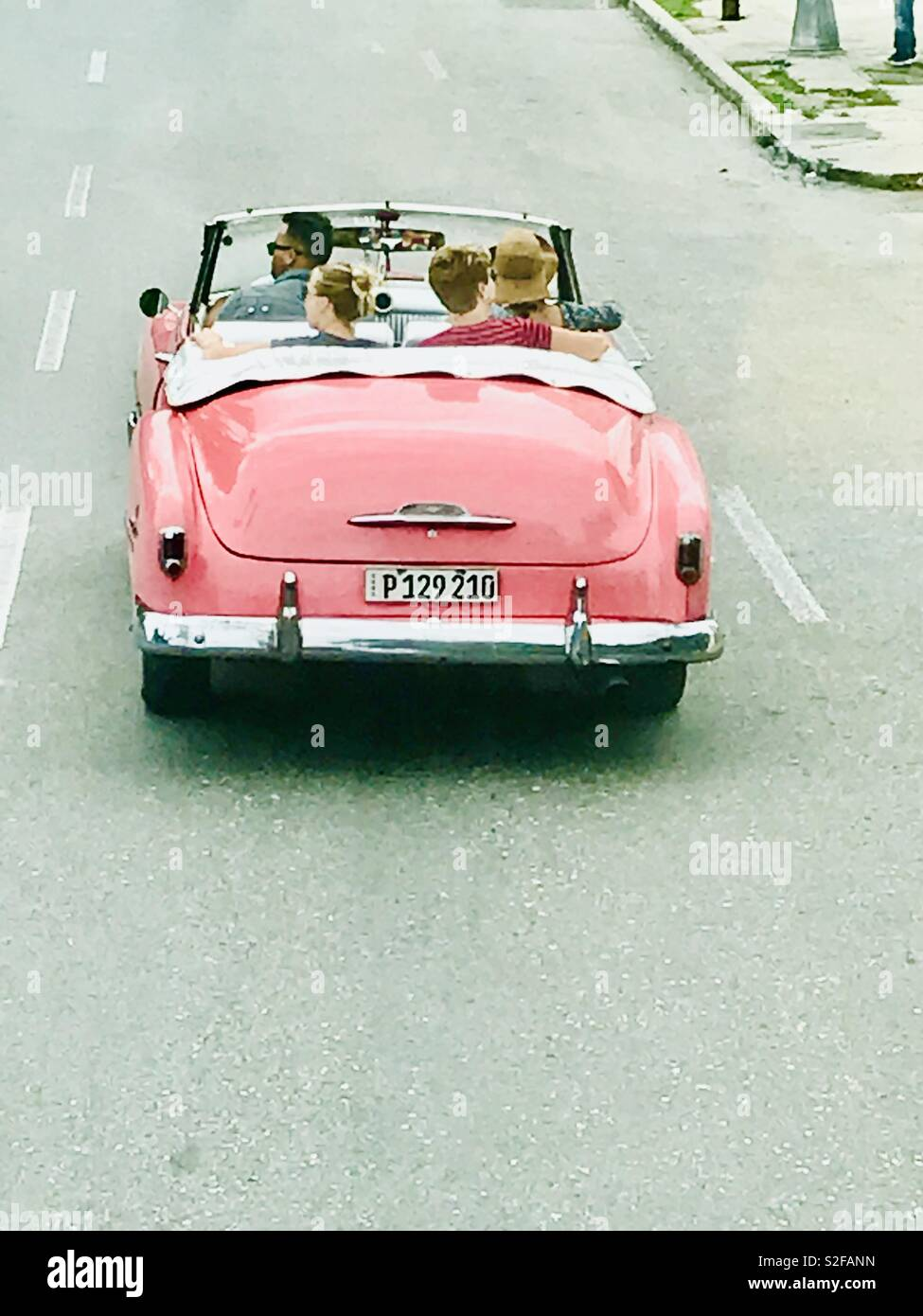 Classic pink Chevrolet cruising with the roof top down along the streets of Havana Cuba - Stock Image