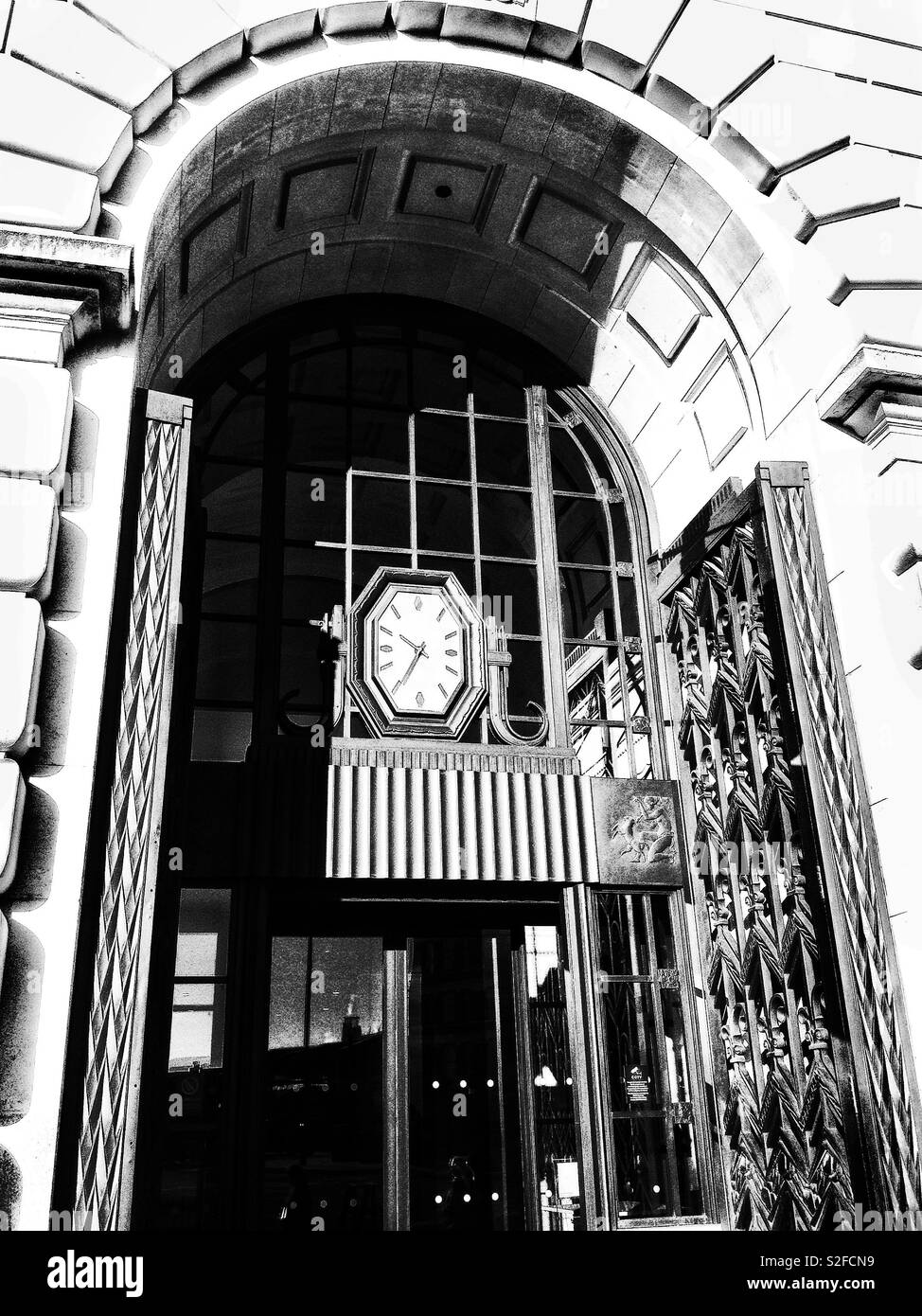 1930's Art Deco entrance to Unilever House, Victoria Embankment, London showing the octagonal clock and ornate metalwork - Stock Image