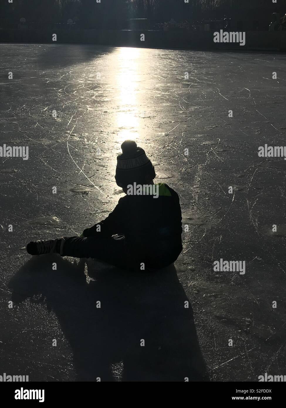 Boy ice skate sunset - Stock Image