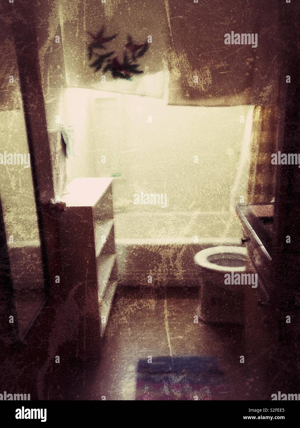Grunge photo of tiny empty apartment bathroom with window light - Stock Image