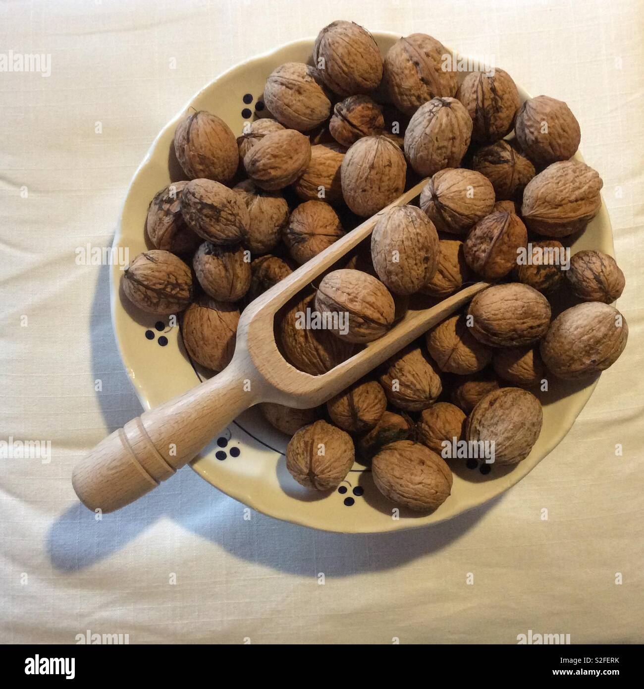View from above on harvested walnuts and wooden chute in vintage ceramic bowl Stock Photo