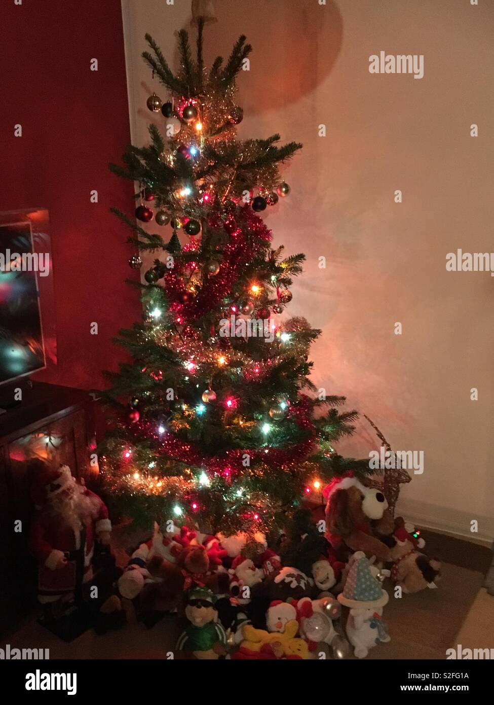 Christmas tree surrounded by novelty soft toys - Stock Image