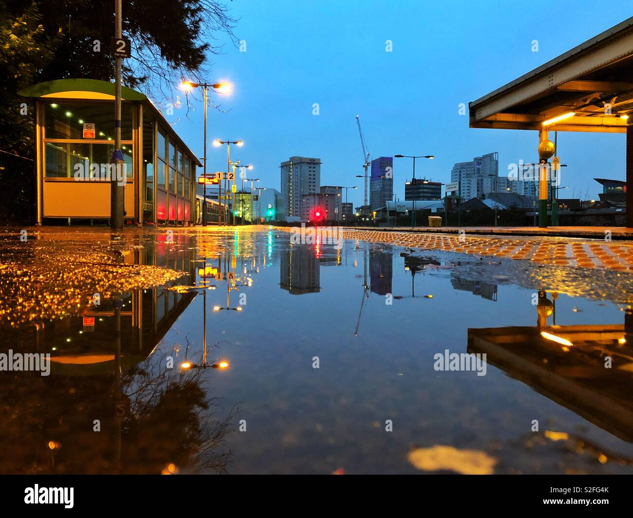 Reflections in a rain puddle on a train platform, Cardiff. - Stock Image
