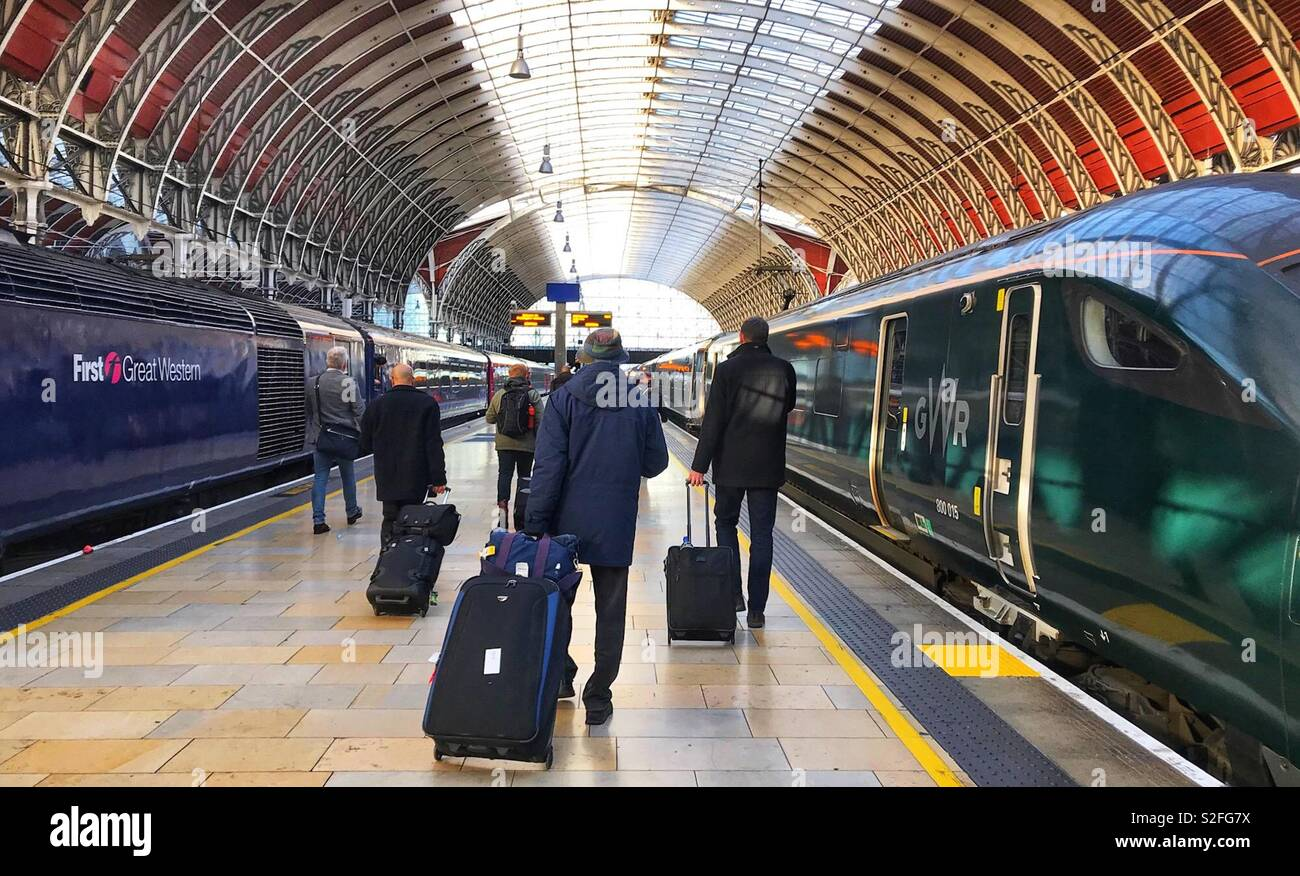 Passengers walking along a platform at London Paddington Station to board an inter city train Stock Photo