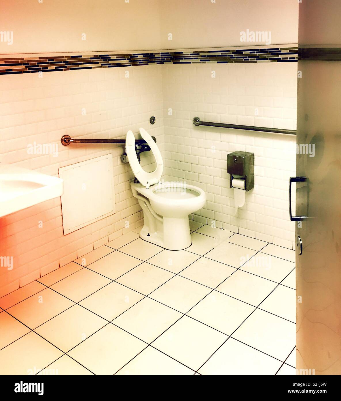 A white public restroom with disability access bars and toilet sizing, USA - Stock Image