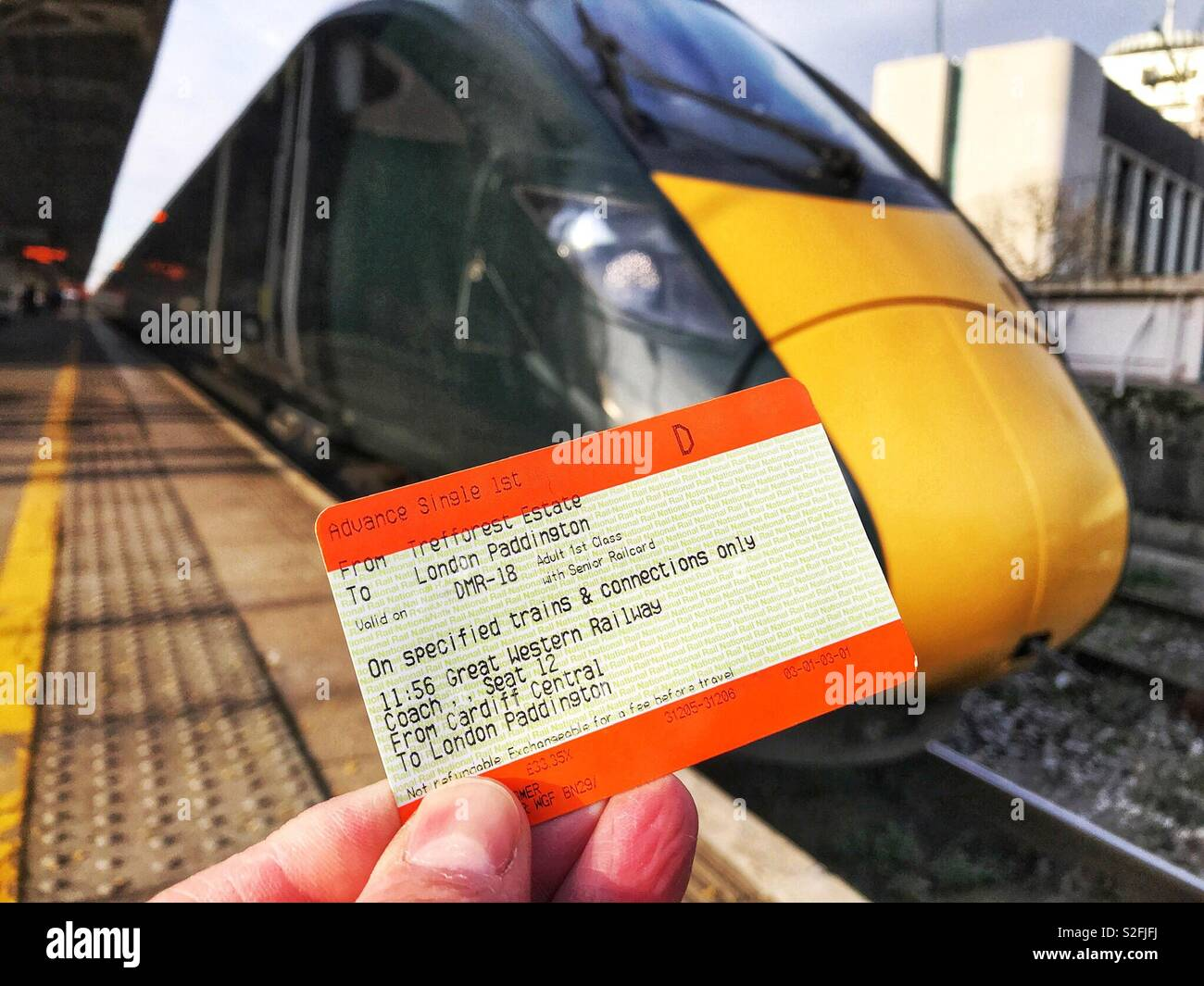 Close up of rail ticket in front of an inter city express train in a station - Stock Image