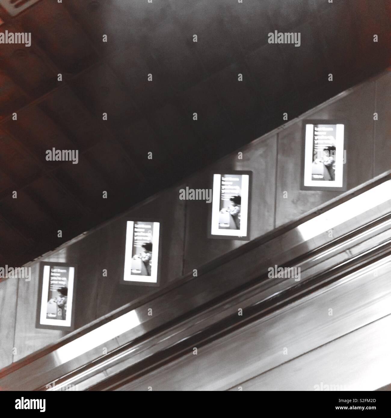 Tube station London Underground posters on wall next to customer escalators - Stock Image