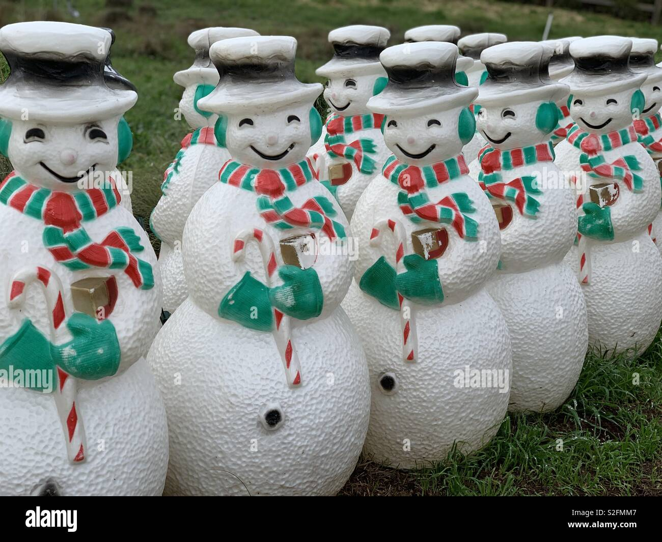 Two rows of plastic snowmen dressed is green and red earmuffs scarf and mittens Stock Photo