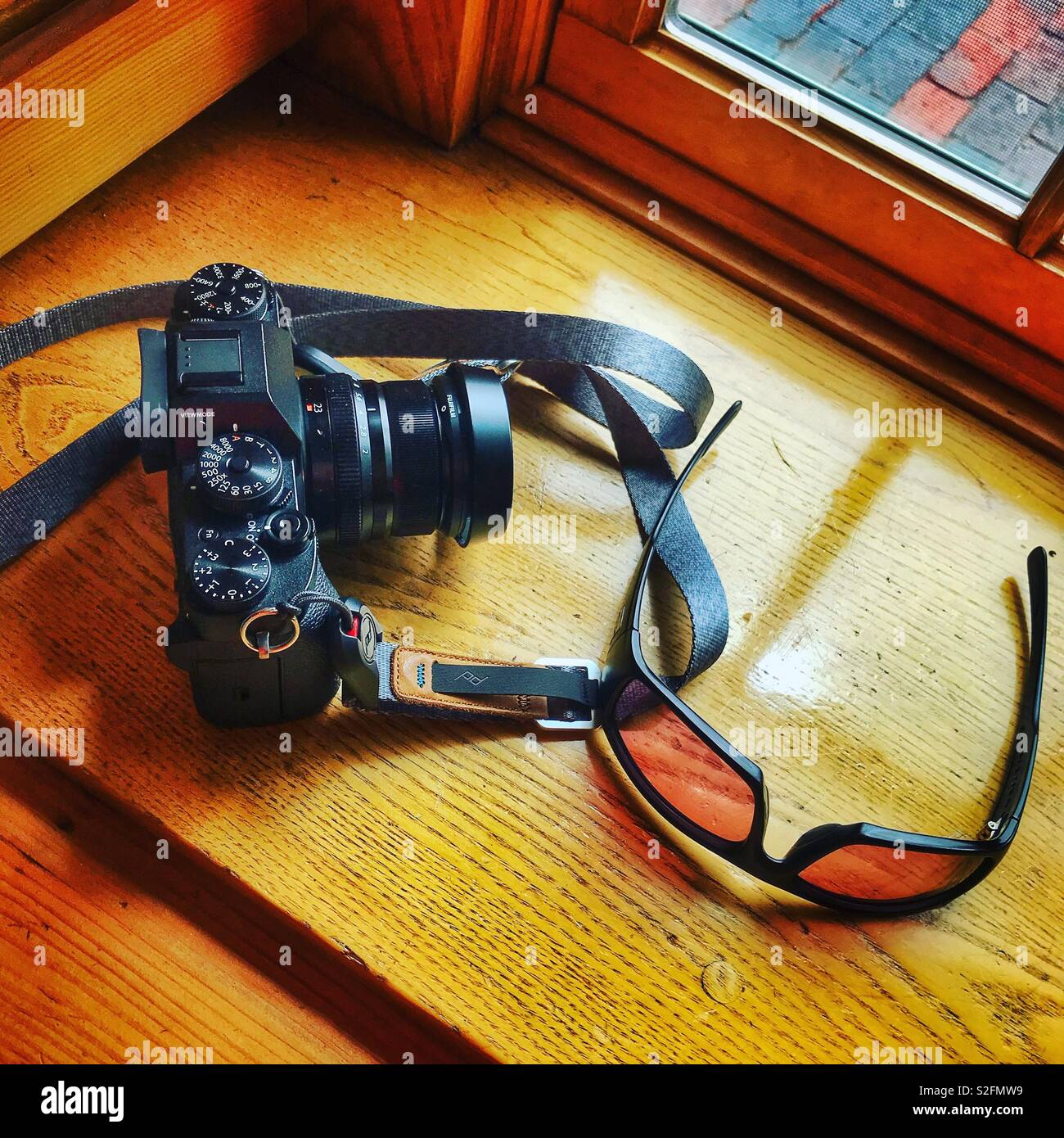 Fujifilm Xt2 with XF23mm lens and Smith sunglasses on a sunny windowsill. - Stock Image