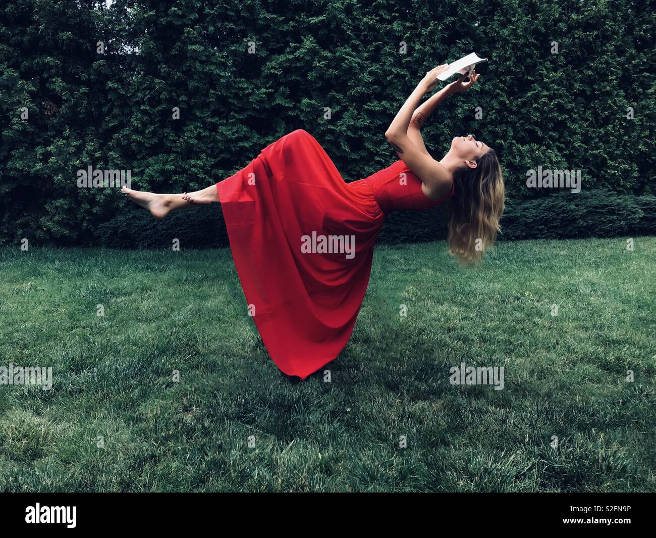 Girl in red dress flying with book - Stock Image