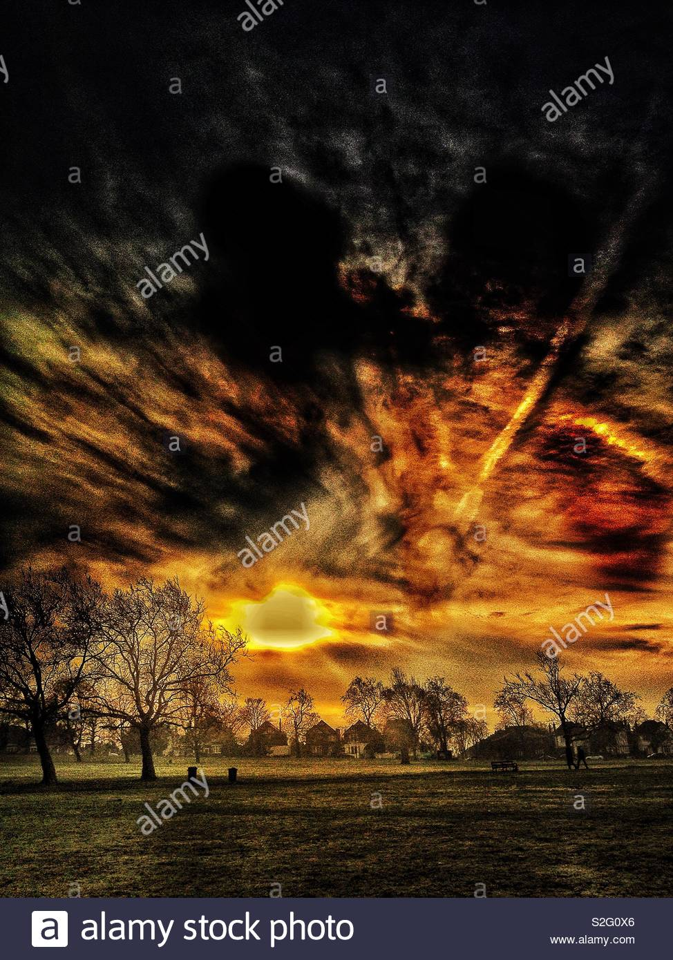 Stylised dramatic winter storm clouds over an open field in suburban London - Stock Image