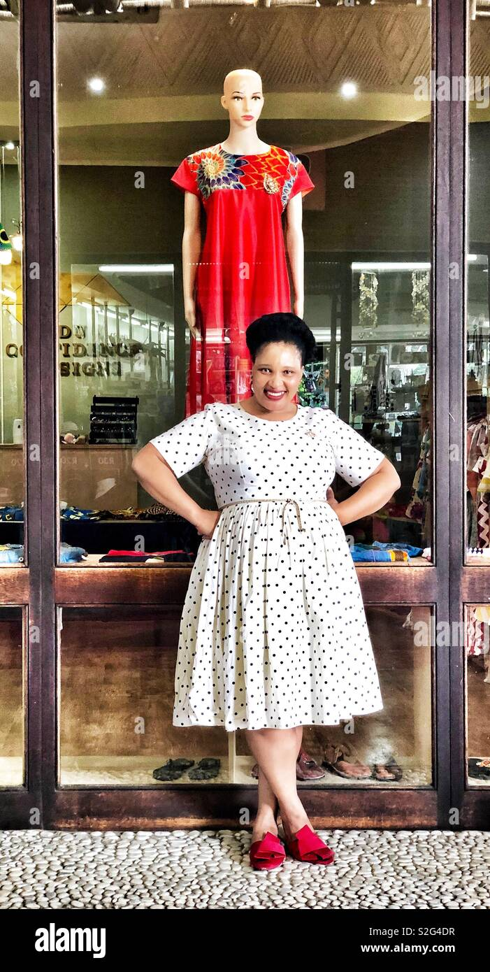 A South African woman posing, wearing a white dress with dots and red sandals at her clothing store in Durban, Sudáfrica. - Stock Image