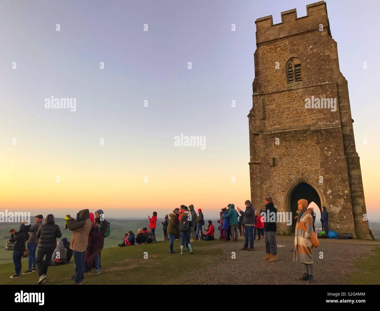 Watching sunrise on New Years Day 2019 at Glastonbury Tor, Somerset - Stock Image