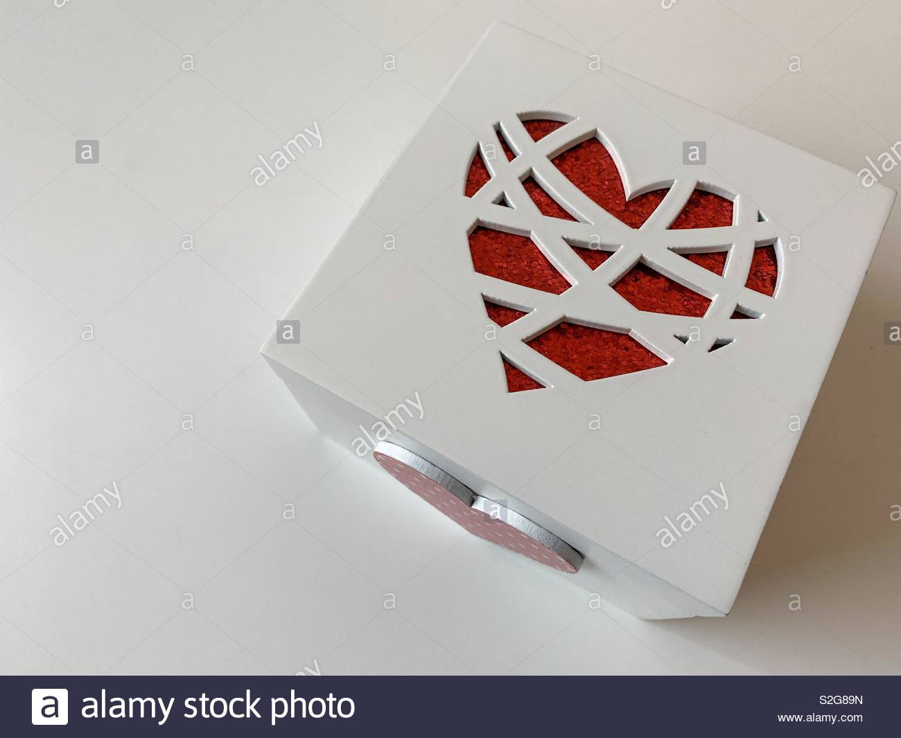 White decorative box with openwork red heart on the top and red wooden heart on the site, isolated on white - Stock Image