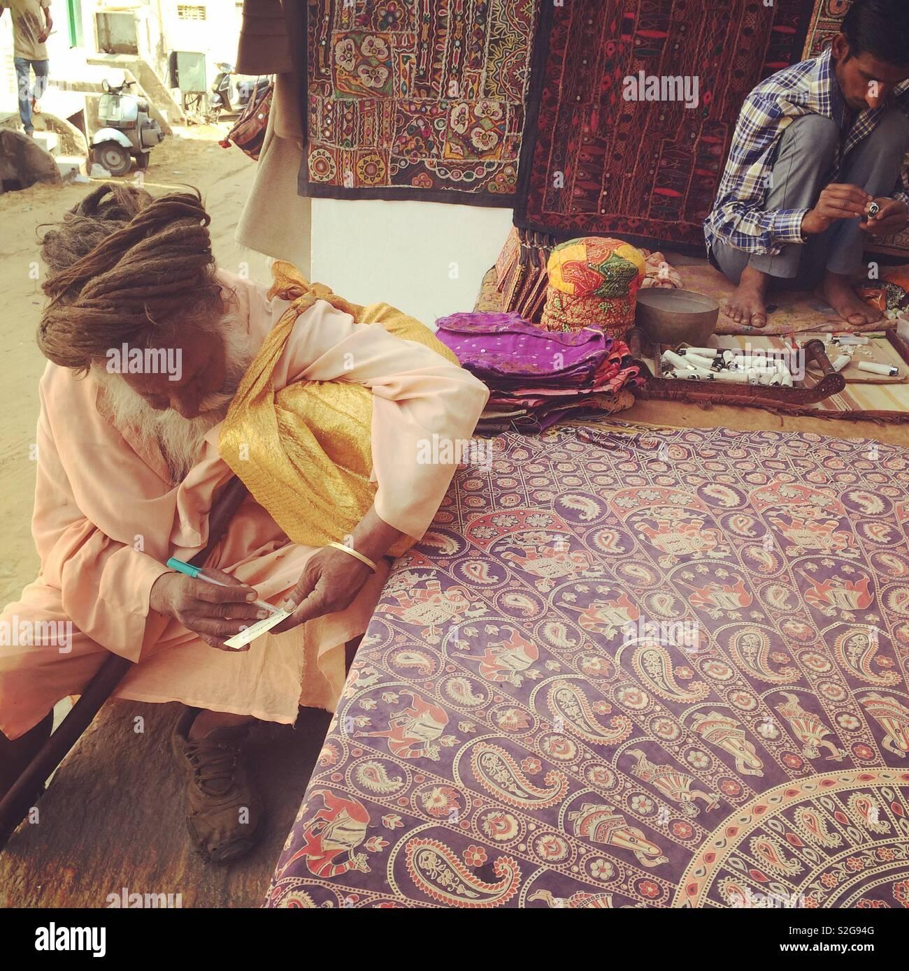 Sadhu in Pushkar with jewelry seller - Stock Image
