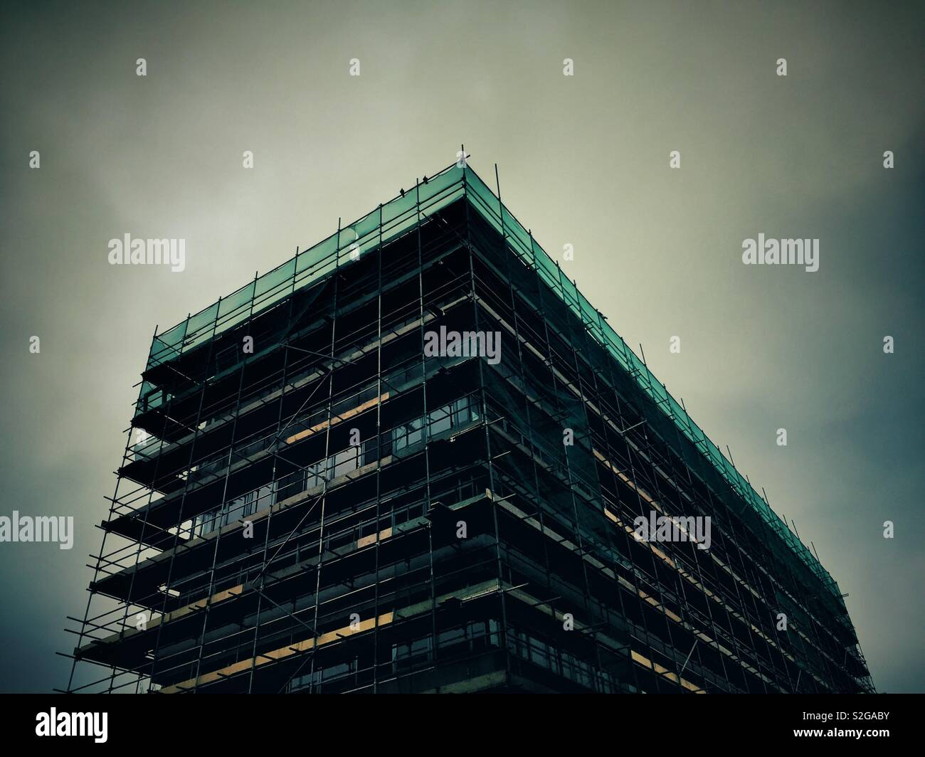 Multi-story building surrounded by scaffolding. - Stock Image