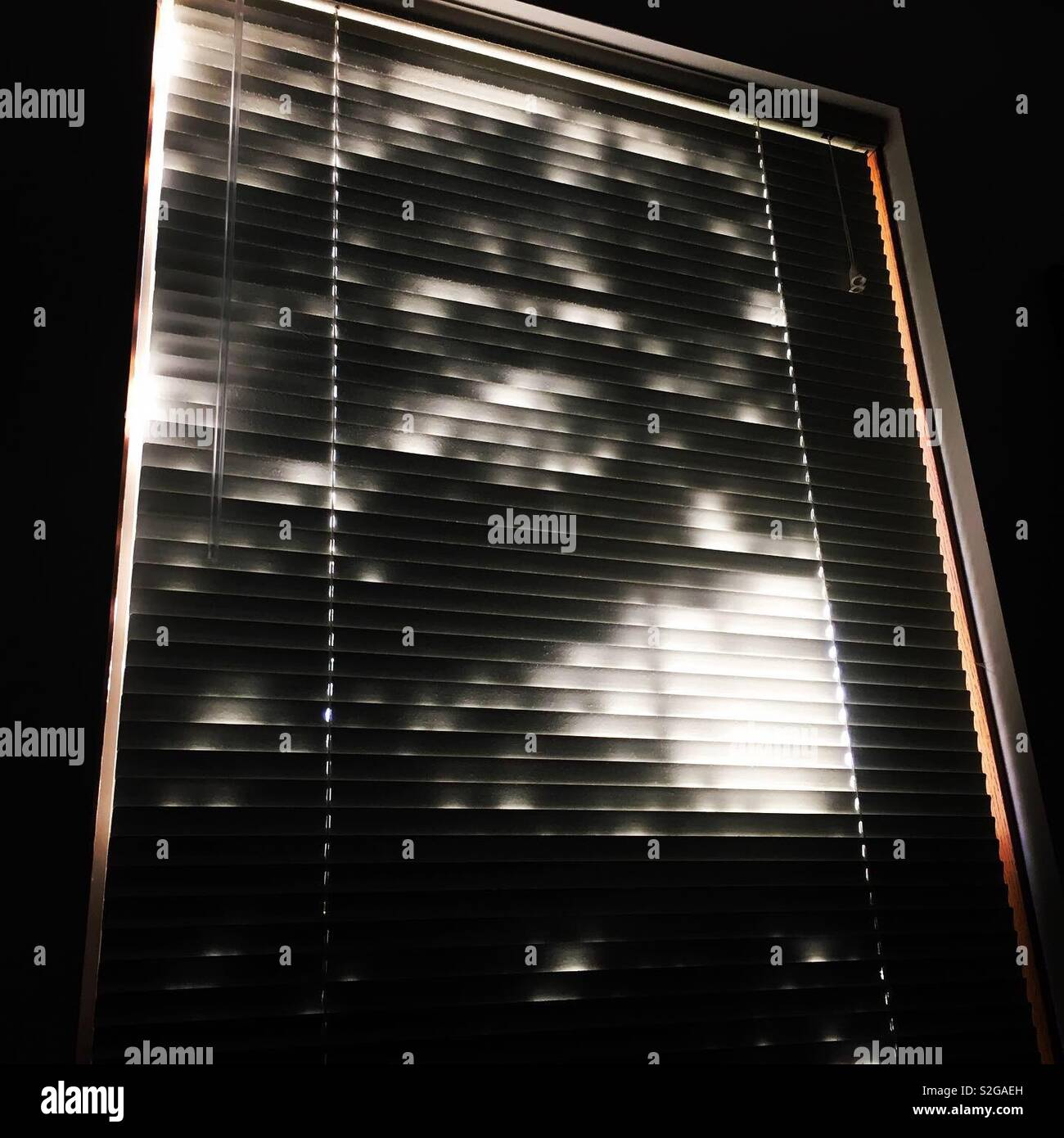 Window with Venetian mini blinds and backlit shadows - Stock Image