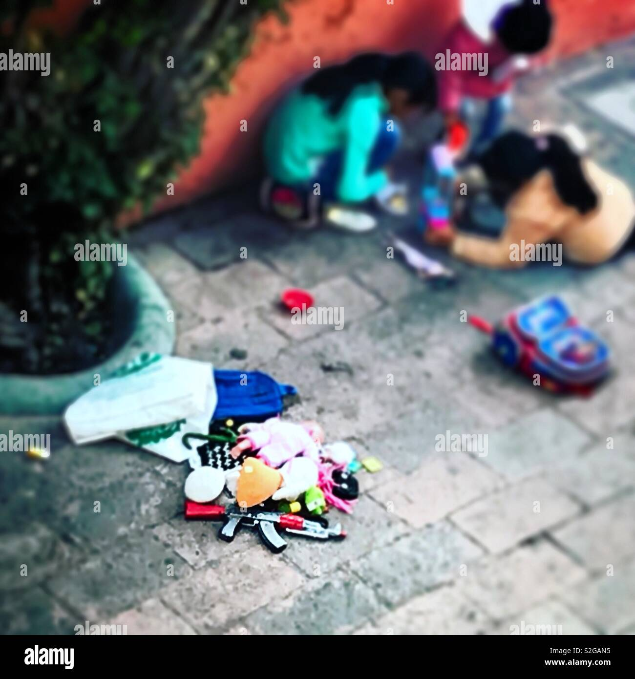 Children play with toys near a toy machine gun in Tequisquiapan, Queretaro, Mexico - Stock Image