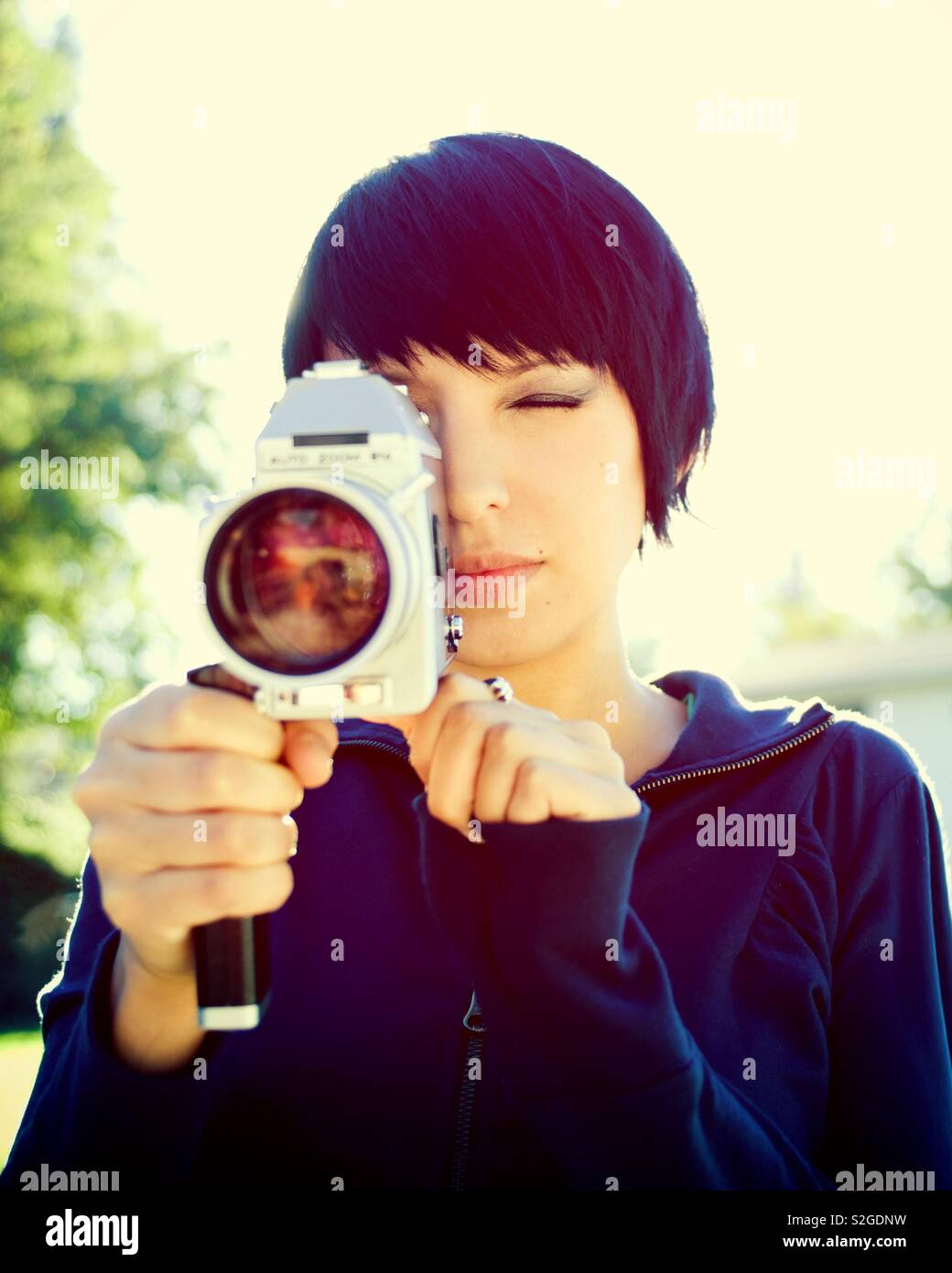 Cute girl with short hair in her early twenties holding a vintage super 8mm film camera outdoors on a sunny day. Photo has a color crossed process effect. - Stock Image