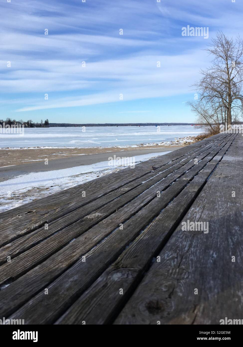 Winter's beach, frozen lake with ice shelters in it. Long wooden bench - Stock Image