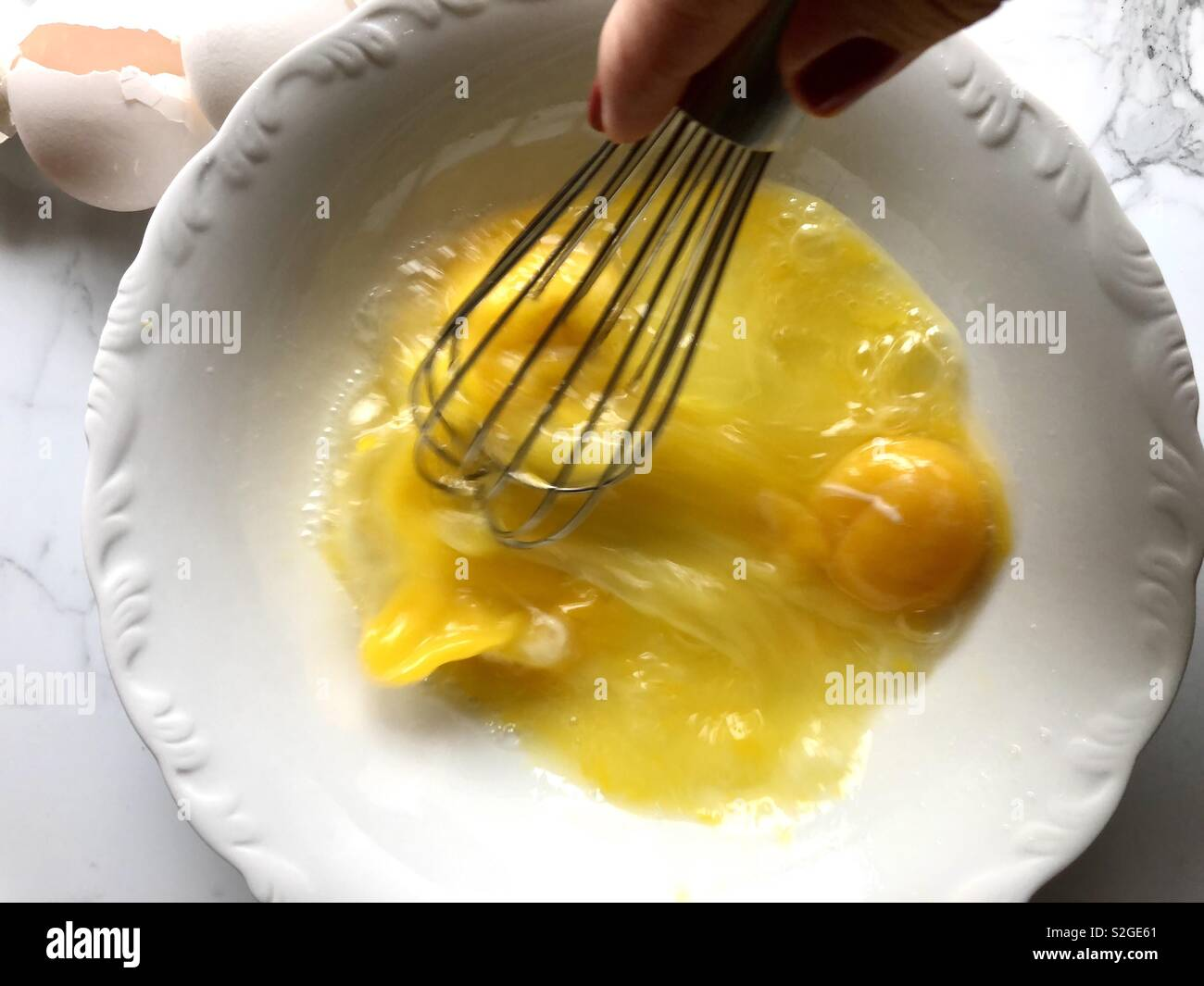 Whisking eggs in a white bowl - Stock Image